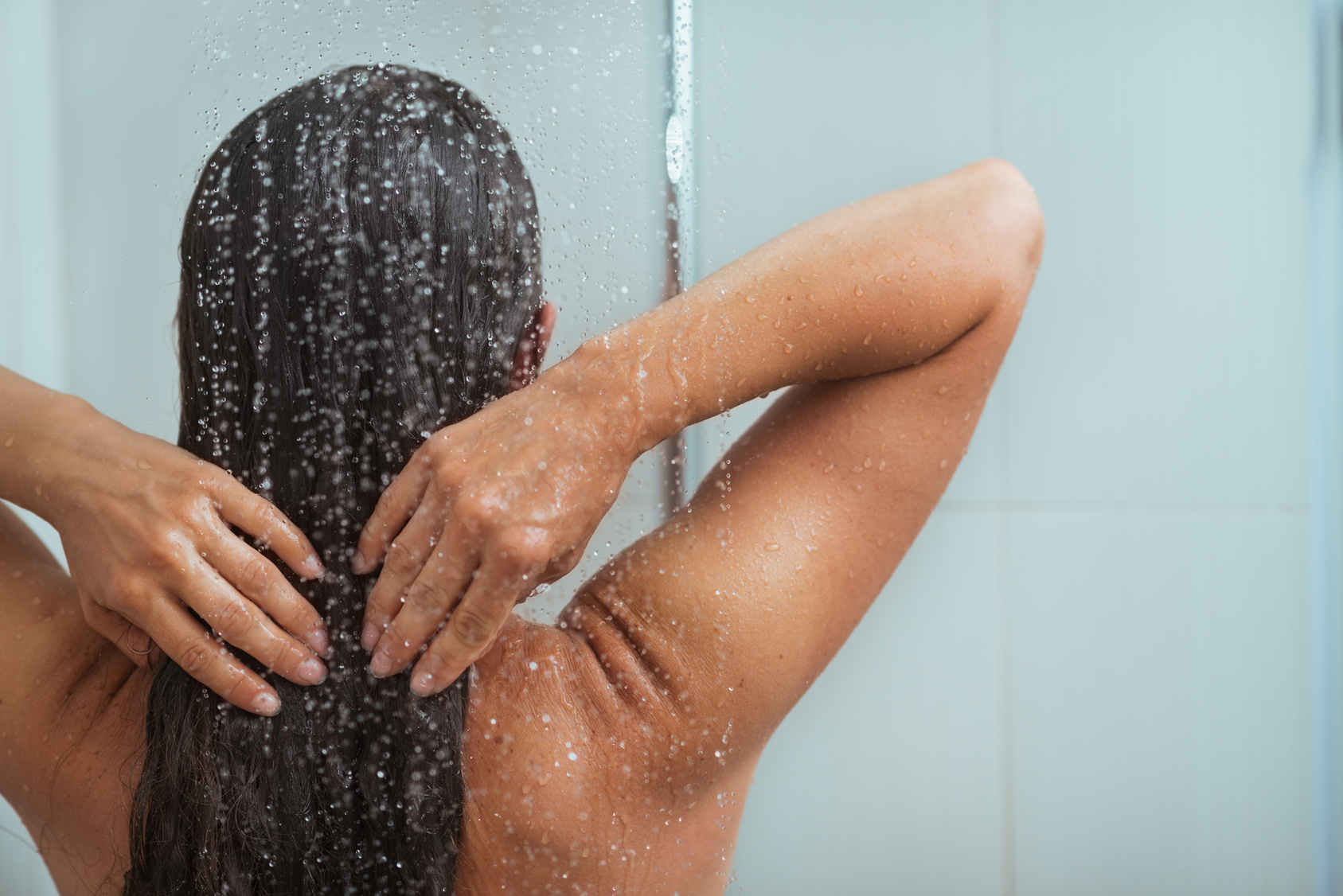 Woman washing long hair in shower under water jet
