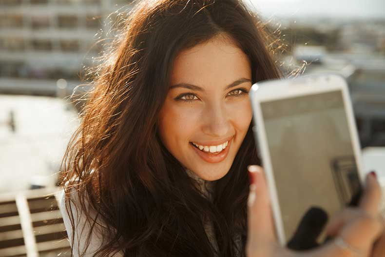 picture-of-smiling-woman-taking-a-selfie-photo