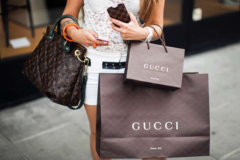 A pedestrian carries Gucci-branded shopping bags as she walks in the Rue du Rhone in Geneva, Switzerland, on Saturday, June 9, 2012. Photographer: Valentin Flauraud/Bloomberg *** Local Caption ***