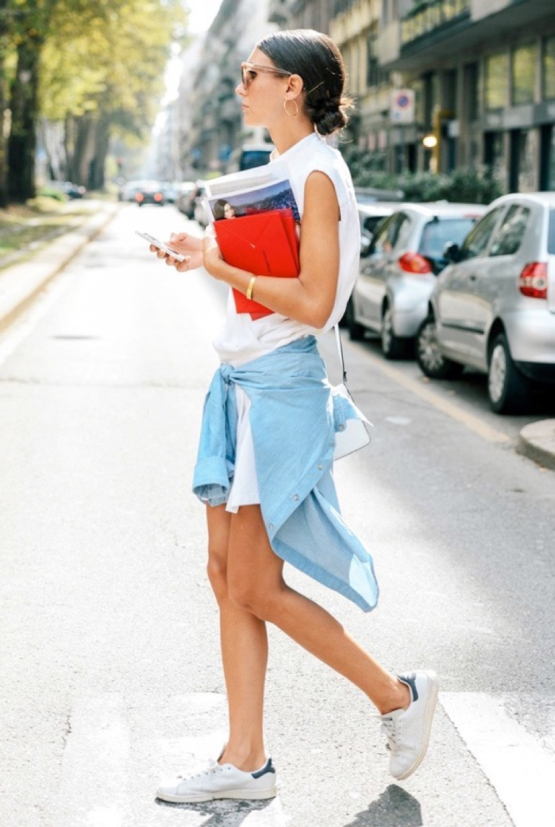 le-fashion-blog-laid-back-street-style-low-bun-hoop-earrings-white-sleeveless-shirtdress-denim-shirt-tied-around-the-waist-adidas-stan-smith-sneakers-via-vogue